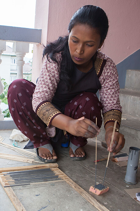 Artisan laying out the painted lina dowels to dry